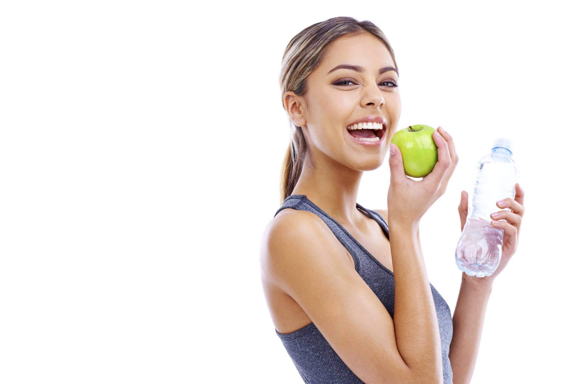 Portrait of a sporty young woman holding an apple and a bottle of water against a white background