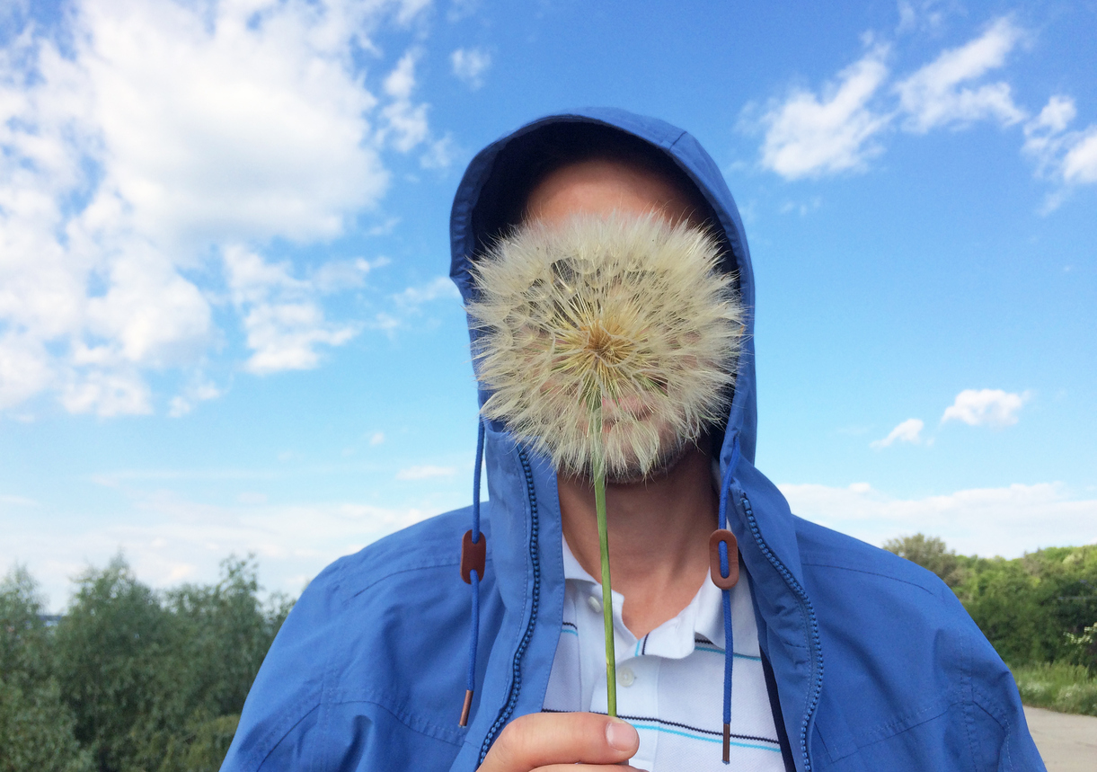 Man covering his face with giant dandelion